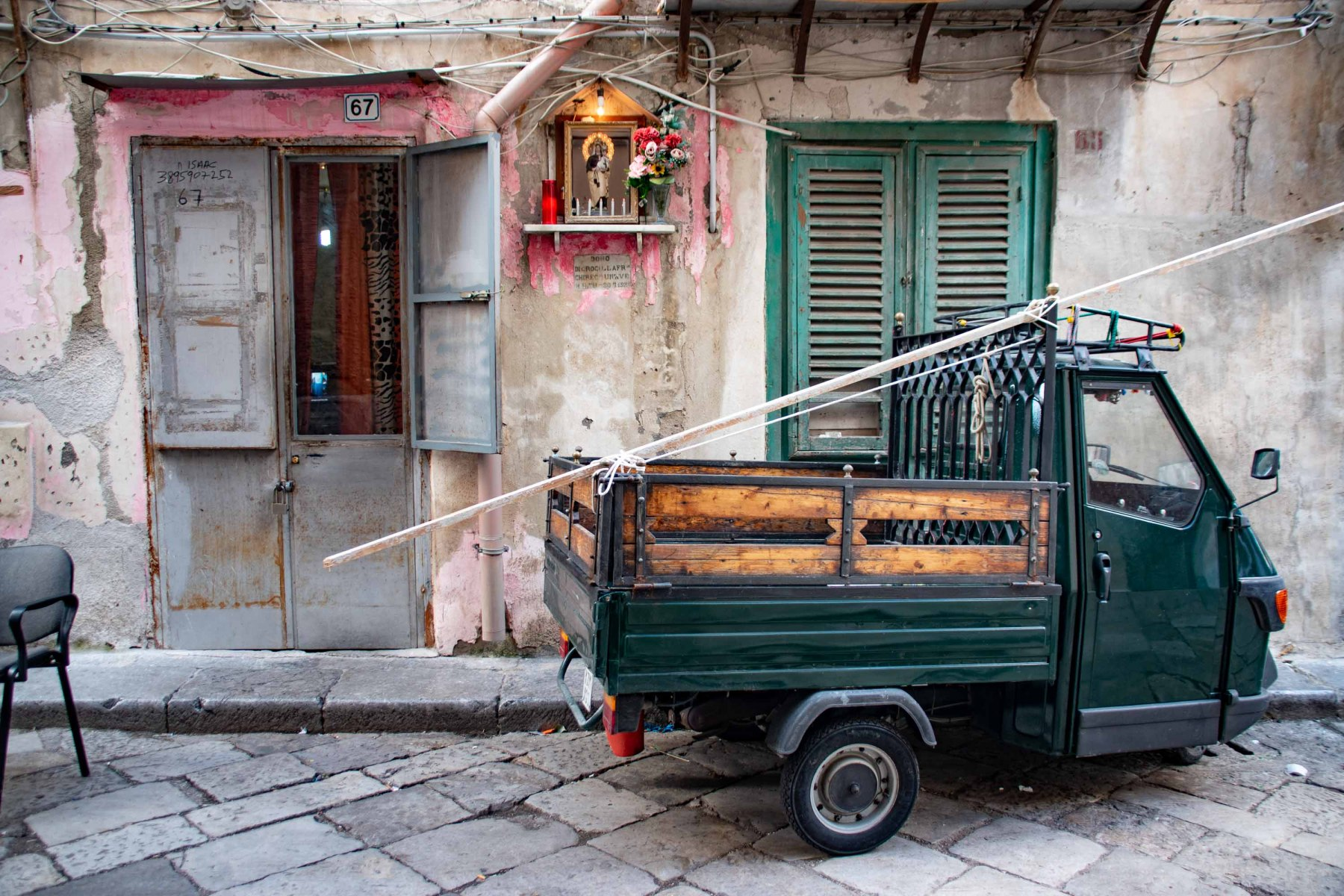 Mini-lorry Ape in front of a house with a religious wayside shrine, seen in Ballarò, Palermo, Sicily, Italy.
